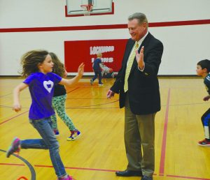 Principal Mike Bowman high-fives Reese Griesmer as she runs and jumps over a series of small obstacles in PE class on Tuesday. (Judy Killen photo)